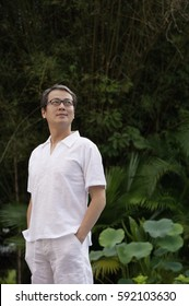 Man in white shirt and pants, standing in garden