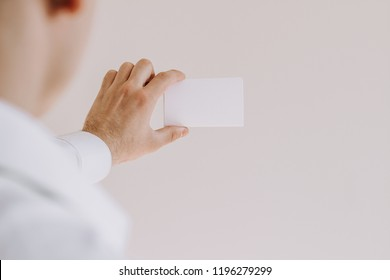 Man in white shirt showing a blank card