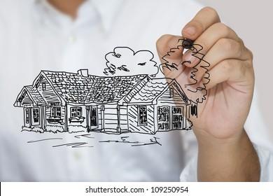 Man in white shirt sketching house