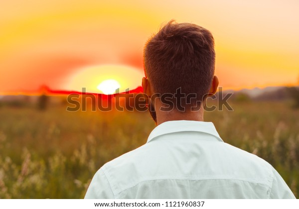 a man in a white shirt stands and looks at the sunset