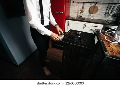 Man in white shirt takes something from the drawer in the kitchen