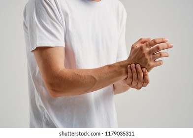 a man in a white shirt touches his hand