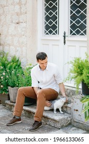 A man in a white shirt and trousers sits on the steps near beautiful white doors and flower pots and strokes a gray cat