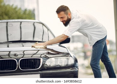 Man in a white shirt. Worker wipes a car. Male holding a rag in his hand