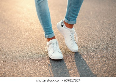 Man in white sneakers on asphalt at sunset. Men's shoes