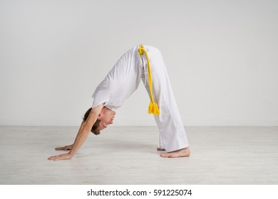 Man in white sports clothes does yoga.