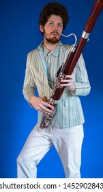 man with a white suit and his bassoon standing in front of a blue wall