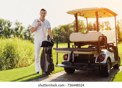 A man in a white suit is smiling and holding a golf club. Next to him is a bag for golf clubs and a golf cart