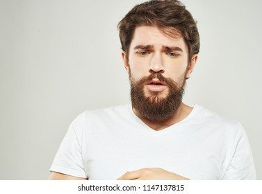 A man in a white T-shirt with a beard portrait.