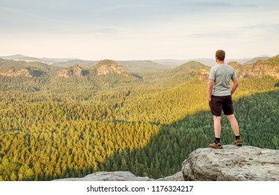 Man in white t-shirt and black outdoor trousers on rocky summit. Hike in mountains, motivation and inspiration in beautiful sunset.