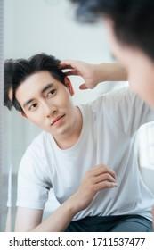 Ein Mann in weißem T-Shirt macht die Frisur, bevor er morgens sein Haus verlässt.