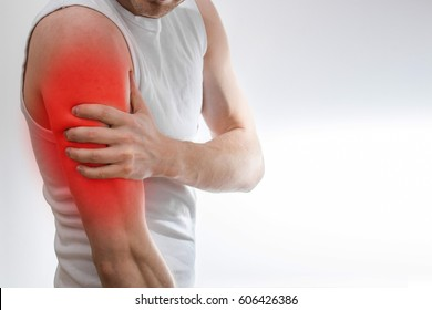 A man in a white T-shirt holds on to the shoulder, arm,  wrist, forearm, sports injury, experiencing pain, on a white background