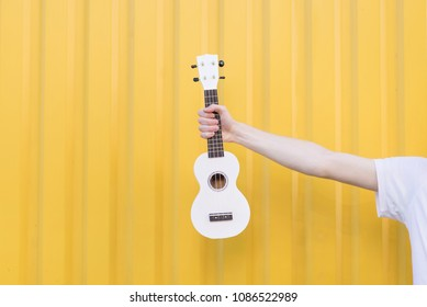 Man in a white T-shirt holds a ukulele against the background of a yellow wall