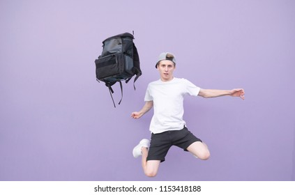 Man in a white T-shirt jumping with a backpack on a purple background.Backpack and a man flying against the background of a purple wall.Young man jumping against the background of a pastel purple wall