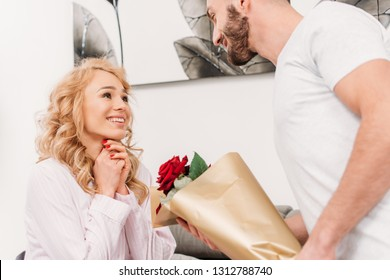 Man in white t-shirt presenting flowers to girlfriend