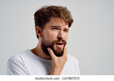 A man in a white T-shirt scratches his beard.