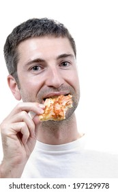 A man in a white t-shirt takes a bite from a slice of pizza.