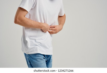 a man in a white t-shirt is touching his belly