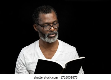 A man in white t-shirt wearing eyeglasses is reading a book