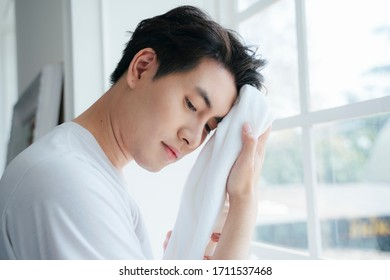 A man in white t-shirt wipe his face after washing by the towel.