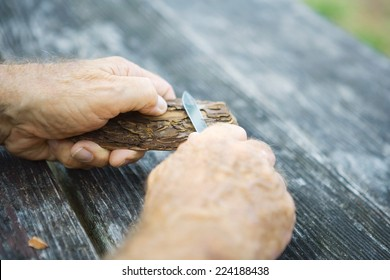 Man whittling piece of bark, cropped view of hands