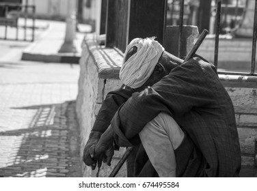 A man who is blind and homeless sitting in front of the mosque and awaiting the mercy of the passersby, no one is sad and unhappy at all.