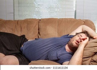 Man who is comfortable resting on the couch all sprawled out