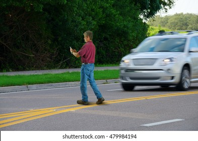 A man who is completely distracted by his cell phone is unaware that he is jaywalking by walking out into heavy traffic on a busy highway road.