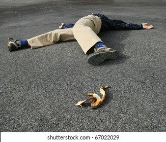 a man who had an accident when he slipped on a banana peel lies on the ground