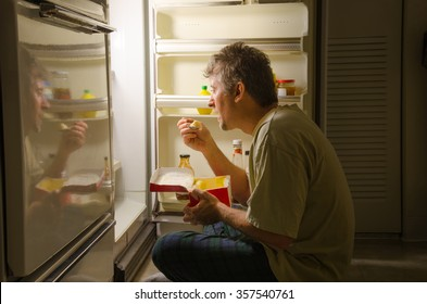 A man who has nighttime sleep-related eating disorder sleep eating as he sits in front of a refrigerator eating ice cream out of carton, oblivious to everything around him as he is actually sleeping.
