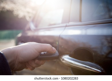 A man who unlocks the car with a smart remote control key.