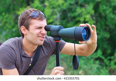 Man who is watching in spotting scope or looking through a telescope