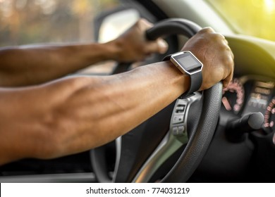 Man who wearing digital sport watch is driving vehicle while working or going to somewhere.