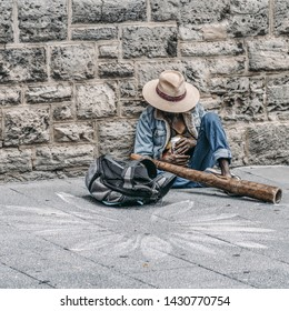 man who wears a hat, jeans and beard drinks a can of beer on the street while laying back. He has a didgeridoo