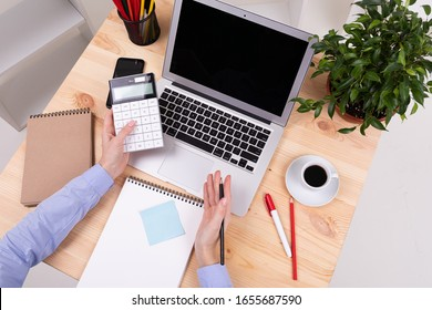 a man who works with laptop, calculator, pens, pencils, card, phone and a plant on his desktop in his office