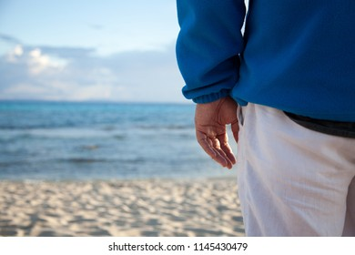 A man whose hand is only visible at dawn observes the seascape