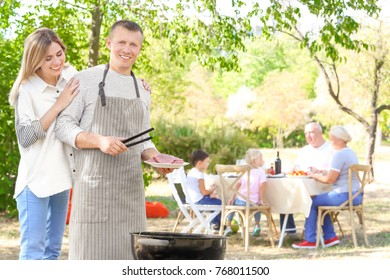 Man with wife cooking tasty steaks on barbecue grill outdoors