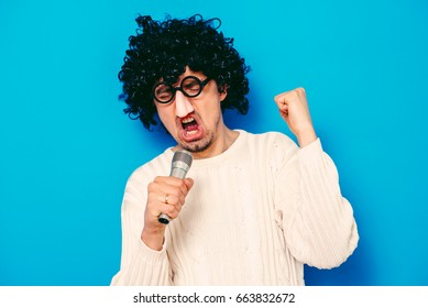 A man in a wig and funny glasses, singing into the microphone