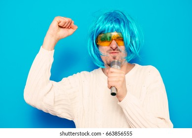 A man in a wig, and sunglasses singing into a microphone.