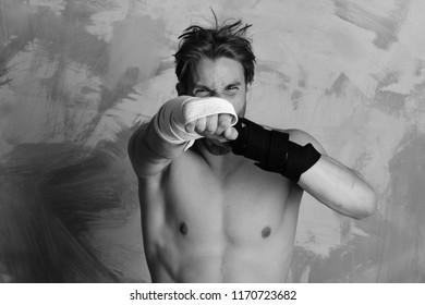 Man with wild face and naked torso on colorful background. Boxer or karate fighter practices martial arts. Guy with black belt and bandage on arms. Healthy lifestyle and jujitsu concept