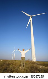 man and wind turbines under blue sky