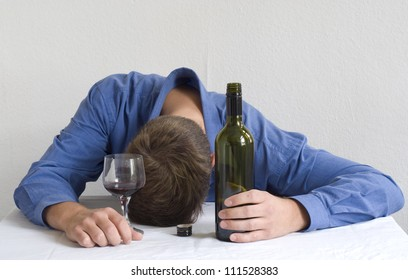 Man with wine bottle and glass, sleeping on the table.