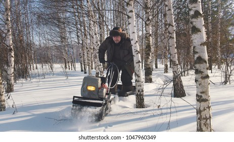 Man in winter clothes fast riding on mini snowmobile on deep snowdrifts in the forest and maneuvering between the trees