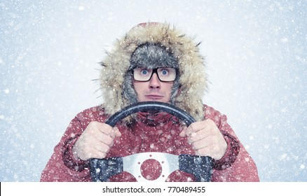 Man in winter clothes with a steering wheel, snow blizzard. Concept car driver
