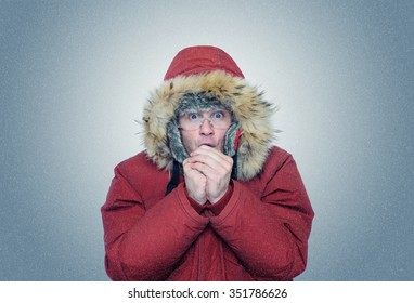 Man in winter clothes warming hands, cold