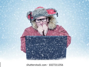 Man in winter clothes warming his hands while sitting in front of laptop. Cold, snow, blizzard