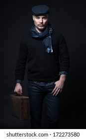 Man winter fashion. Wearing black sweater with scarf and cap. Holding vintage suitcase. Blonde hair and beard. Studio shot against dark wall.