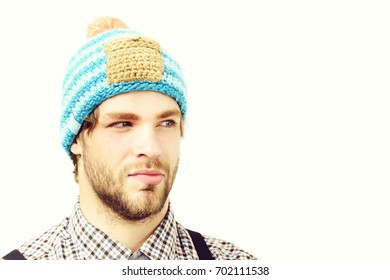 Man in winter hat and plaid shirt isolated on white background. Bearded man with suspicious face wears hat. Guy with stylish hat in blue beige and orange color. Winter and casual style clothes concept