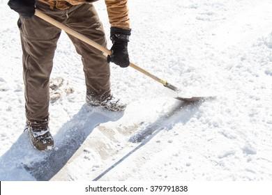 A man in winter ships and scrapes hard ice from the frozen driveway with a shovel