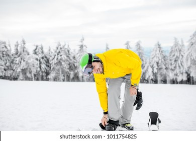 Man in winter sports clothing wearing a snowboard outdoors on the snowy mountains